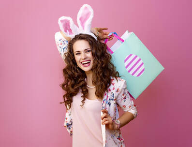 Smiling woman on pink background with Easter shopping bag